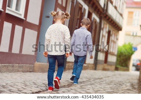 Two happy children walking in sunny town