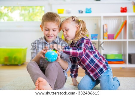 Two happy clever children exploring ball globe