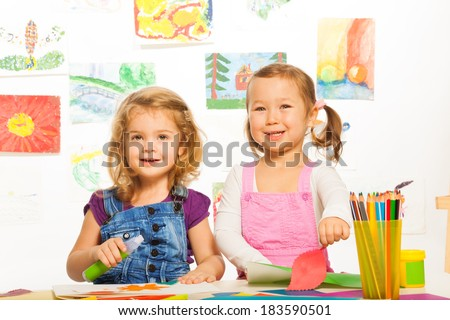 Two happy color little girls cutting and gluing with pictures on background - stock photo