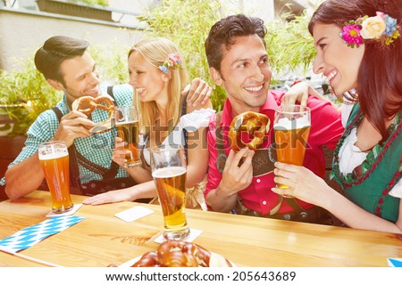 Two happy couples in beer garden in summer with pretzel and beer - stock photo