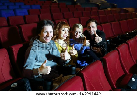 Two happy couples look at camera and thumb up in cinema theater. Focus on left pair.