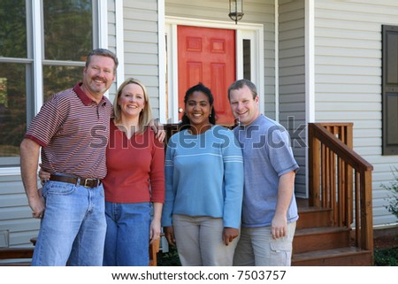 Two happy couples standing outside a new home - stock photo
