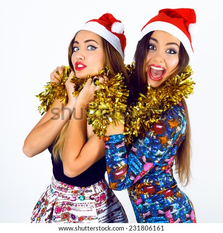 Two happy crazy best friends girls ready for celebrating New Year party, holding tinsel screaming  and having fun, wearing bright fashion holiday outfits and santa hats. Positive mood and emotions. - stock photo