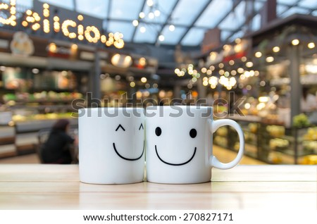 Two happy cups on coffee store blur background - stock photo