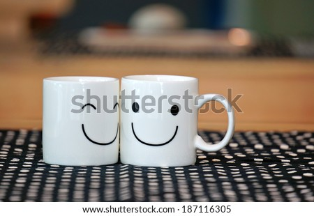 Two happy cups on wood table with black polka dot tablecloth. Concept about love and relationship                     - stock photo