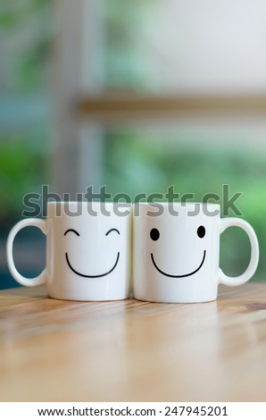 Two happy cups on wood table with bokeh, about love concept - stock photo