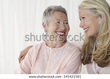 Two happy elegant senior women looking at each other against white background - stock photo