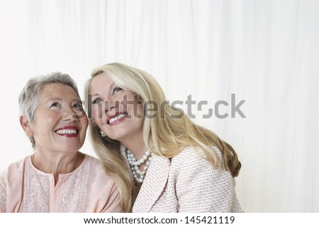 Two happy elegant senior women looking up against white background - stock photo
