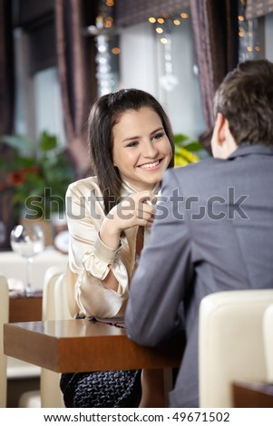 Two happy enamoured sit at restaurant - stock photo