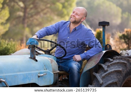 Two happy farmers talking near the agricultural machinery at shed  - stock photo