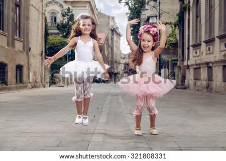 Two happy fashion little ballerinas on the street - stock photo