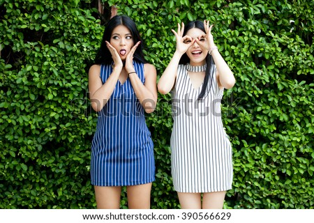 Two happy female best friends having fun with crazy and playful expressions on green bush background - stock photo