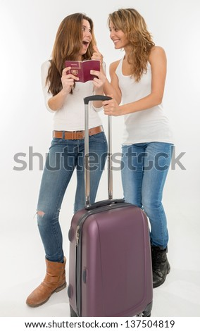 Two happy female friends with suitcase and passport - stock photo