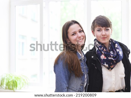 Two happy female students near the window in classroom - stock photo