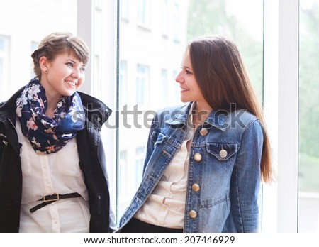 Two happy female students talking near the window in classroom - stock photo