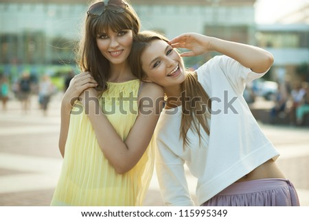 two happy females laugh and have good time together - stock photo