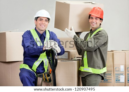 Two happy foremen loading cardboard boxes at warehouse - stock photo