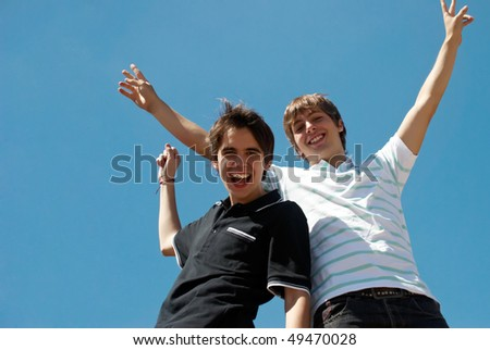 Two happy friends against the sky - stock photo