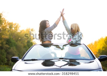 Two happy friends driving modern luxury cabriolet car on vacation on summer day. Beautiful cheerful young ladies giving high five, having fun together, cheering with raised arms - stock photo