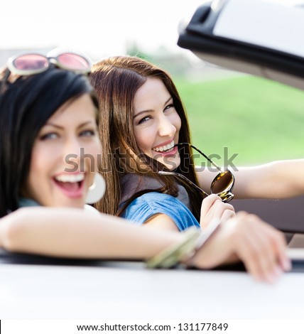 Two happy friends in the cabriolet driving everywhere and looking for freedom and fun - stock photo