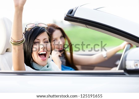 Two happy friends in the white car driving everywhere and looking for freedom and fun - stock photo
