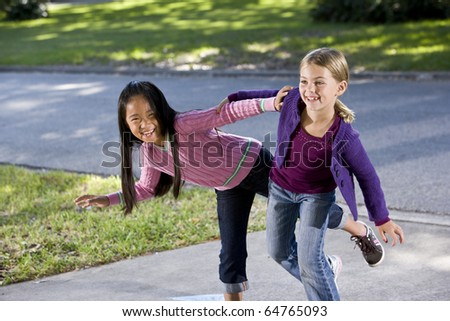 Two happy friends playing  on driveway - girls 7 years - stock photo