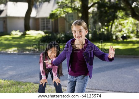 Two happy friends playing  outdoors - girls 7 years, focus on girl in foreground - stock photo
