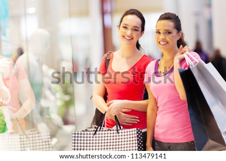 two happy friends shopping in mall - stock photo