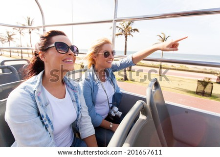 two happy friends taking city bus touring the town - stock photo
