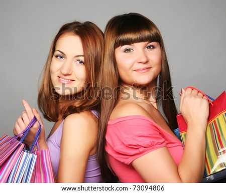 two happy girlfiends with shopping bags - stock photo
