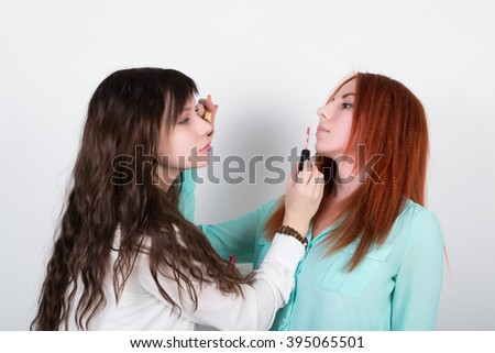 Two happy girlfriends doing makeup to each other