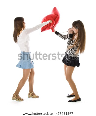 Two happy girlfriends fighting a pillows. Isolated on white background