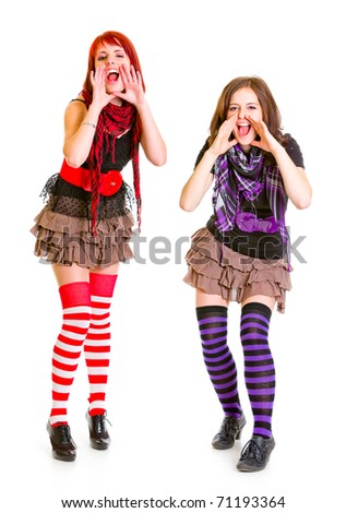 Two happy girlfriends shouting through  megaphone shaped  hands isolated on white - stock photo