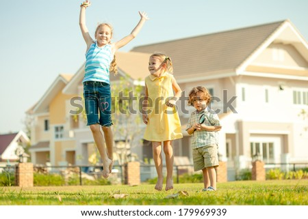 two happy  girls and little boy jumping on the nature - stock photo