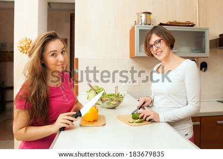 two happy girls cut fresh vegetables in the kitchen - stock photo