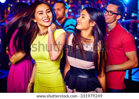 Two happy girls dancing in nightclub on background of their friends
