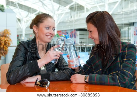Two happy girls drink water in food court in a mall