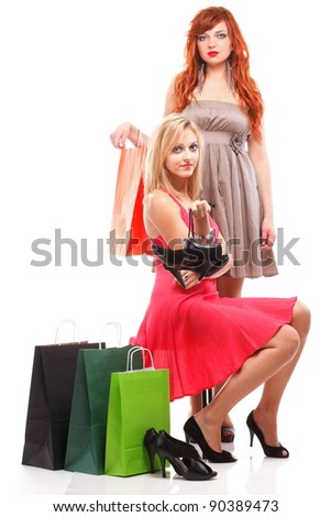 two happy girls ginger and blonde with shopping bags shoes over white - stock photo