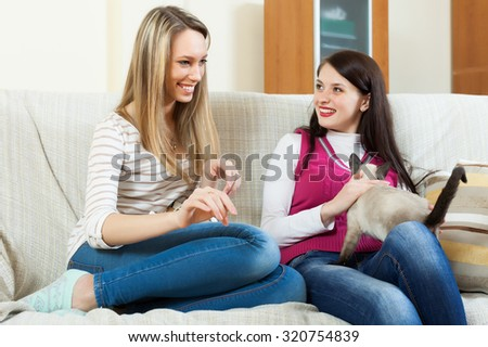 two happy girls  gossiping   in home interior - stock photo