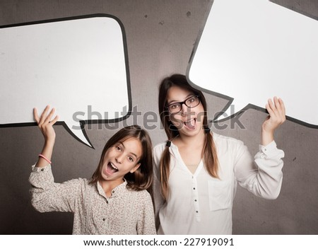 two happy girls holding a speech bubble - stock photo
