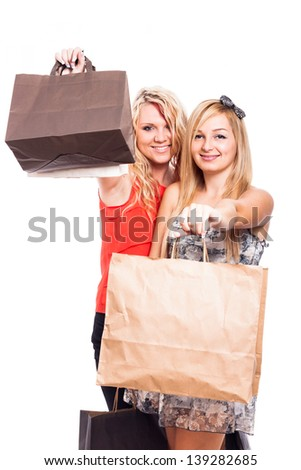 Two happy girls holding shopping bags, isolated on white background - stock photo