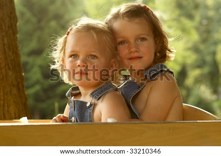 Two happy girls in a wooden wagon