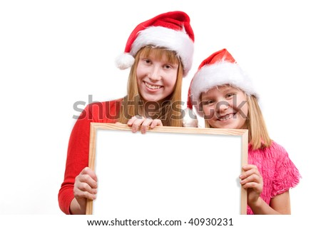 Two happy girls in red santa hats holding empty board - stock photo