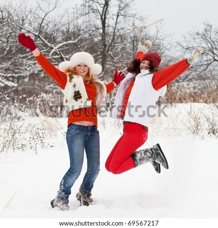 Two happy girls is jumping at  winter park - stock photo