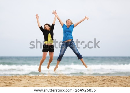 Two happy girls jumping on the beach against the sea and cloudless sky. Shallow depth of field. Focus on the model. - stock photo