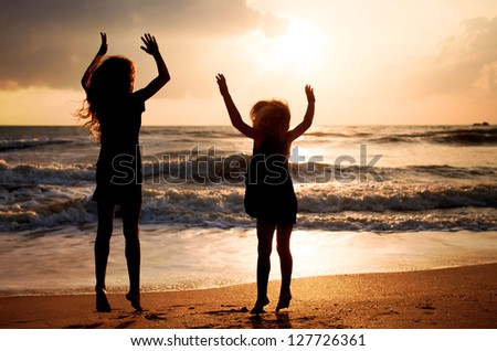 Two happy girls jumping on the beach on the dawn time