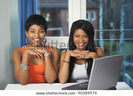 Two happy girls on laptop browsing a favorite online service - stock photo