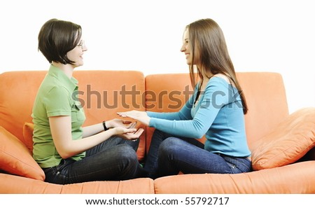 two happy girls play game with hands isolated on white or orange sofa