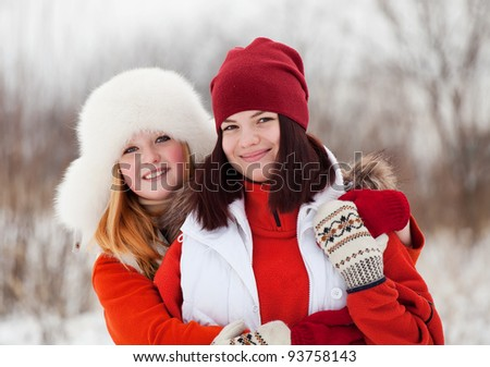 Two happy girls plays in winter park - stock photo