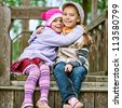 Two happy girls-preschoolers laughs and plays in city children's park. - stock photo